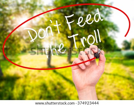 Man Hand writing Don't Feed the Troll with black marker on visual screen. Isolated on background. Business, technology, internet concept. Stock Photo - stock photo