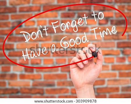 Man Hand writing Don't Forget to Have a Good Time with black marker on visual screen. Isolated on bricks. Business, technology, internet concept. Stock Photo - stock photo