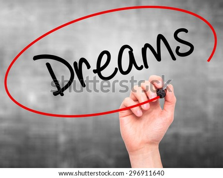 Man Hand writing Dreams with black marker on visual screen. Isolated on grey. Business, technology, internet concept. Stock Photo