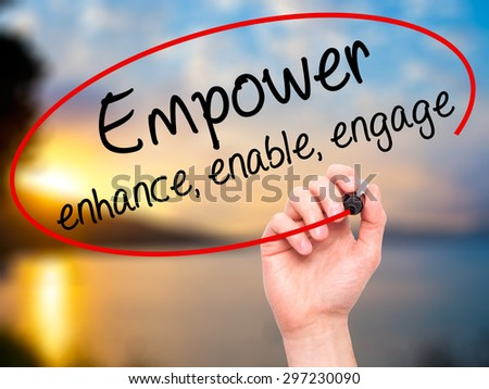 Man Hand writing Empower enhance, enable, engage with black marker on visual screen. Isolated on nature. Business, technology, internet concept. Stock Photo - stock photo