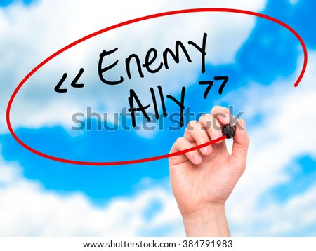 Man Hand writing Enemy - Ally with black marker on visual screen. Isolated on background. Business, technology, internet concept. Stock Photo