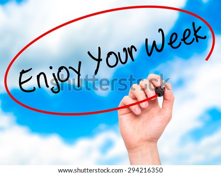 Man Hand writing Enjoy Your Week with black marker on visual screen. Isolated on sky. Business, technology, internet concept. Stock Photo - stock photo