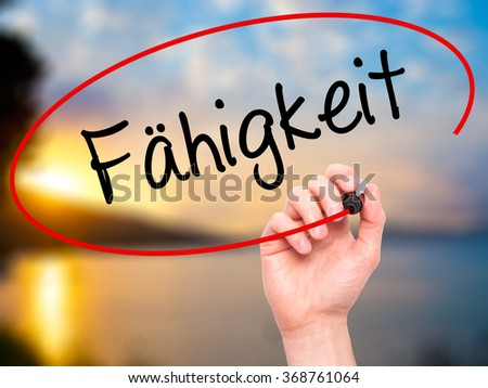 Man Hand writing Fahigkeit (Ability in German) with black marker on visual screen. Isolated on background. Business, technology, internet concept. Stock Photo - stock photo