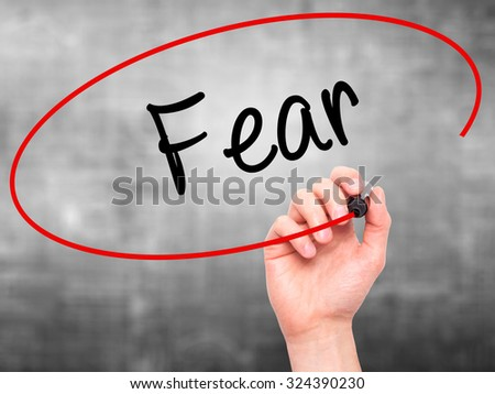 Man Hand writing Fear with black marker on visual screen. Isolated on grey. Business, technology, internet concept. Stock Photo