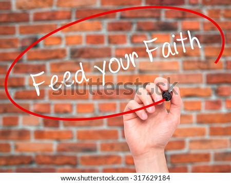 Man Hand writing Feed your Faith with black marker on visual screen. Isolated on bricks. Business, technology, internet concept. - stock photo