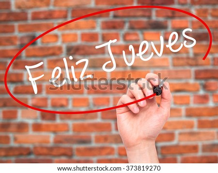 Man Hand writing Feliz Jueves (Happy Thursday In Spanish) with black marker on visual screen. Isolated on background. Business, technology, internet concept. Stock Photo - stock photo