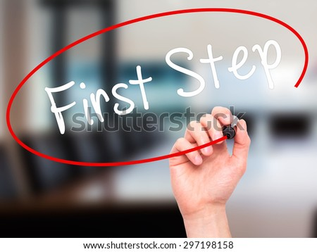 Man Hand writing First Step  with black marker on visual screen. Isolated on office. Business, technology, internet concept. Stock Photo