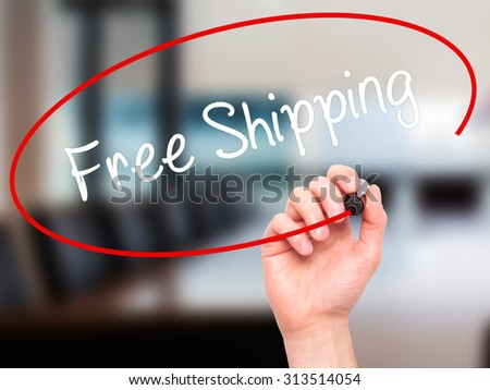 Man Hand writing Free Shipping with black marker on visual screen. Isolated on office. Business, technology, internet concept. Stock Photo - stock photo