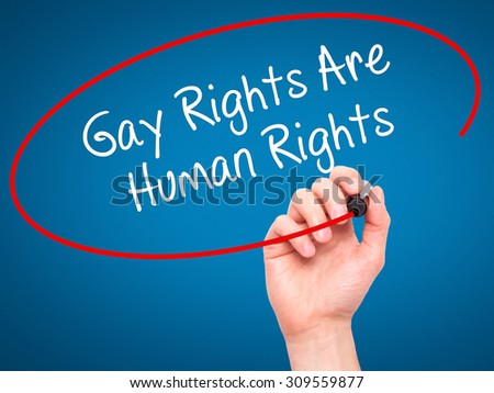 Man Hand writing Gay Rights Are Human Rights  with black marker on visual screen. Isolated on blue. Business, technology, internet concept. Stock Photo