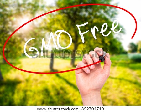 Man Hand writing GMO Free  with black marker on visual screen. Isolated on background. Business, technology, internet concept. Stock Photo - stock photo
