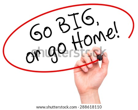 Man Hand writing Go Big or Go Home with black marker on visual screen. Isolated on white. Business, technology, internet concept. Stock Image - stock photo