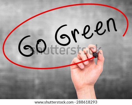 Man Hand writing Go Green with black marker on visual screen. Isolated on grey. Business, technology, internet concept. Stock Image