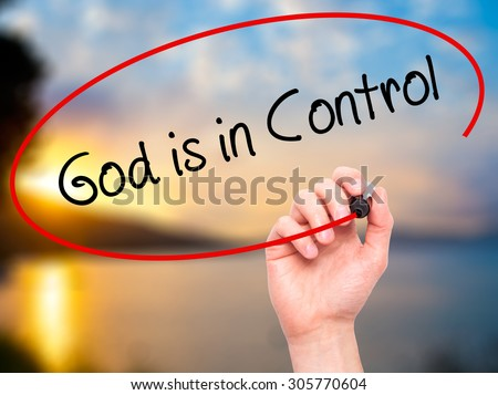 Man Hand writing God is in Control with black marker on visual screen. Isolated on nature. Business, technology, internet concept. Stock Photo - stock photo