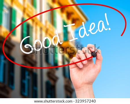 Man Hand writing Good Idea! with black marker on visual screen. Isolated on city. Business, technology, internet concept. Stock Photo - stock photo