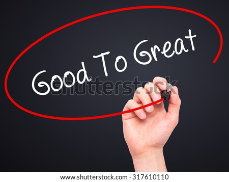 Man Hand writing Good To Great with black marker on visual screen. Isolated on black. Business, technology, internet concept. - stock photo