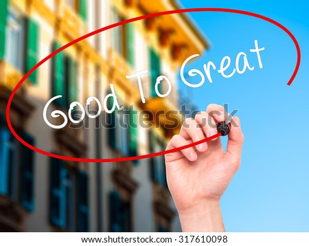 Man Hand writing Good To Great with black marker on visual screen. Isolated on city. Business, technology, internet concept. - stock photo