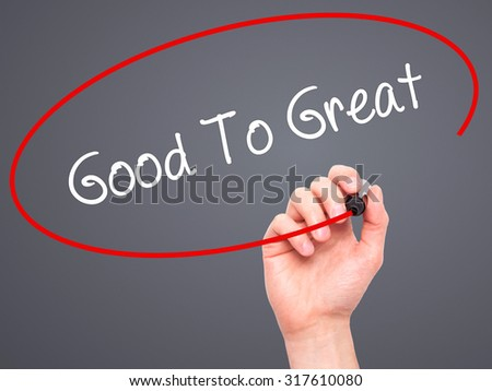Man Hand writing Good To Great with black marker on visual screen. Isolated on grey. Business, technology, internet concept. - stock photo