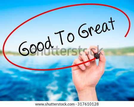 Man Hand writing Good To Great with black marker on visual screen. Isolated on nature. Business, technology, internet concept. - stock photo