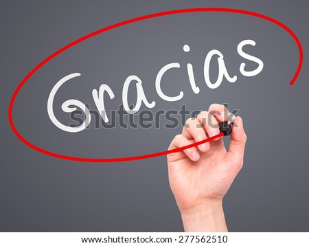Man Hand writing Gracias with marker on transparent wipe board. Isolated on grey. Business, internet, technology concept.  Stock Photo - stock photo