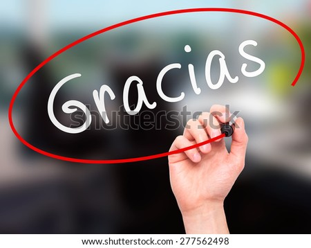 Man Hand writing Gracias with marker on transparent wipe board. Isolated on office. Business, internet, technology concept.  Stock Photo - stock photo