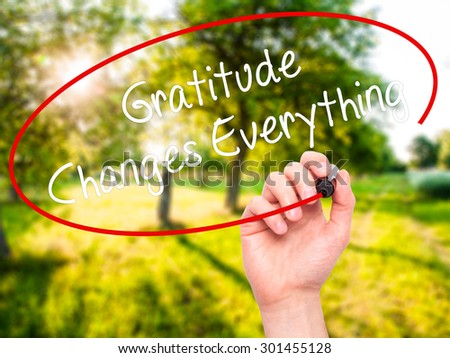 Man Hand writing Gratitude Changes Everything with black marker on visual screen. Isolated on nature. Business, technology, internet concept. Stock Photo - stock photo