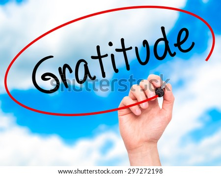 Man Hand writing Gratitude with black marker on visual screen. Isolated on sky. Business, technology, internet concept. Stock Photo - stock photo