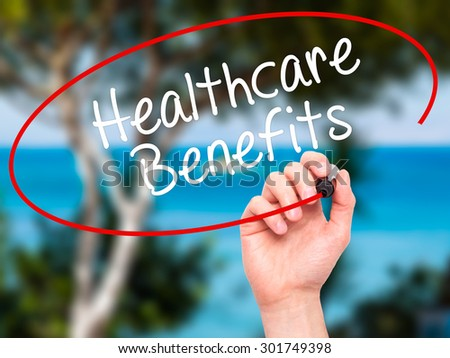 Man Hand writing Healthcare Benefits with black marker on visual screen. Isolated on nature. Business, technology, internet concept. Stock Photo - stock photo
