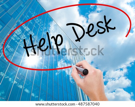 Man Hand writing Help Desk with black marker on visual screen.  Business, technology, internet concept. Modern business skyscrapers background. Stock Photo
