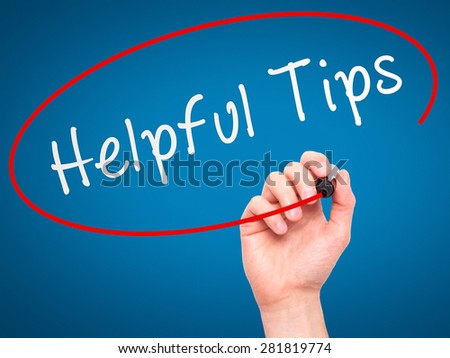 Man hand writing Helpful Tips on visual screen. Business,help, internet, technology concept. Isolated on blue. Stock Photo - stock photo