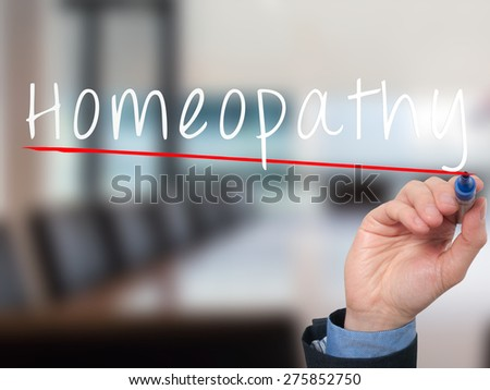 Man Hand writing Homeopathy with marker on transparent wipe board. Health, nature concept. Stock Image - stock photo