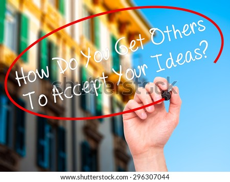 Man Hand writing How Do You Get Others To Accept Your Ideas? with black marker on visual screen. Isolated on city. Business, technology, internet concept. Stock Photo - stock photo