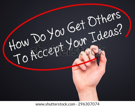 Man Hand writing How Do You Get Others To Accept Your Ideas? with black marker on visual screen. Isolated on black. Business, technology, internet concept. Stock Photo - stock photo