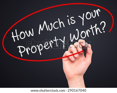 Man Hand writing How Much is your Property Worth? with black marker on visual screen. Isolated on black. Business, technology, internet concept. Stock Image