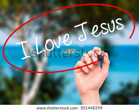 Man Hand writing I Love Jesus with black marker on visual screen. Isolated on nature. Business, technology, internet concept. Stock Photo - stock photo