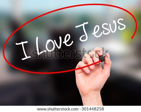Man Hand writing I Love Jesus with black marker on visual screen. Isolated on office. Business, technology, internet concept. Stock Photo - stock photo
