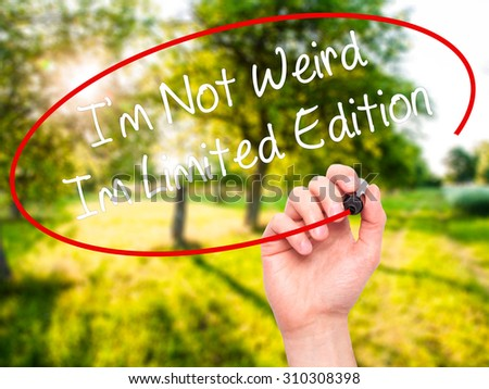 Man Hand writing I'm Not Weird Im Limited Edition with black marker on visual screen. Isolated on nature. Business, technology, internet concept. Stock Photo - stock photo