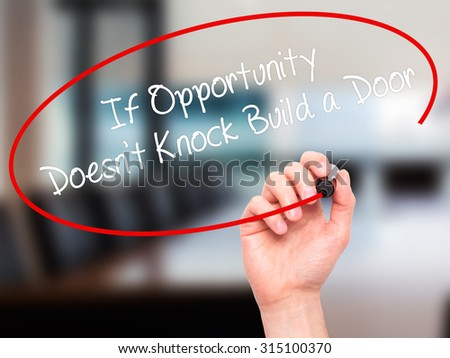 Man Hand writing If Opportunity Doesn't Knock Build a Door with black marker on visual screen. Isolated on office. Business, technology, internet concept. Stock Photo - stock photo