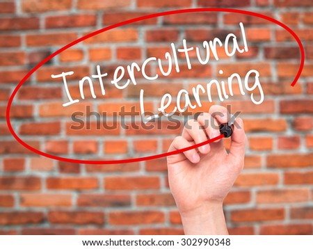 Man Hand writing Intercultural Learning with black marker on visual screen. Isolated on bricks. Business, technology, internet concept. Stock Photo - stock photo
