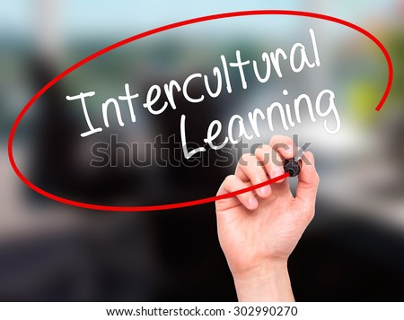 Man Hand writing Intercultural Learning with black marker on visual screen. Isolated on office. Business, technology, internet concept. Stock Photo - stock photo