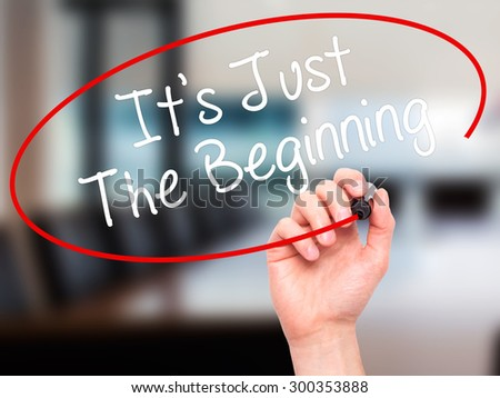 Man Hand writing It's Just The Beginning with black marker on visual screen. Isolated on office. Business, technology, internet concept. Stock Photo - stock photo