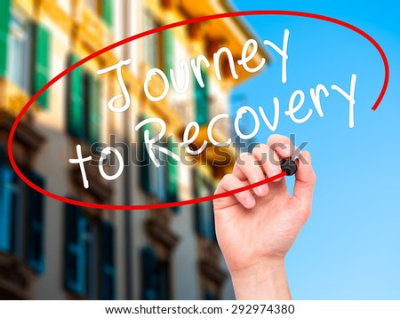 Man Hand writing Journey to Recovery with black marker on visual screen. Isolated on city. Life, technology, internet concept. Stock Image - stock photo