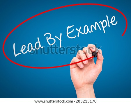Man Hand writing Lead By Example with marker on transparent wipe board. Isolated on blue. Business, internet, technology concept. Stock Photo - stock photo