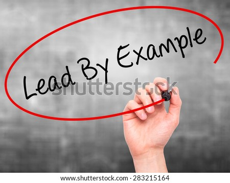 Man Hand writing Lead By Example with marker on transparent wipe board. Isolated on grey. Business, internet, technology concept. Stock Photo - stock photo