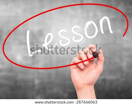 Man Hand writing Lesson with black marker on visual screen. Isolated on grey. Business, technology, internet concept. Stock Image