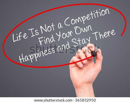 Man Hand writing Life Is Not a Competition Find Your Own Happiness and Stay There  with black marker on visual screen. Isolated on background. Business, technology, internet concept. Stock Photo