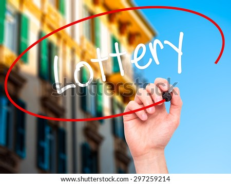 Man Hand writing Lottery  with black marker on visual screen. Isolated on city. Business, technology, internet concept. Stock Photo - stock photo