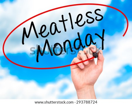 Man Hand writing Meatless Monday with black marker on visual screen. Isolated on sky. Life, technology, internet concept. Stock Image - stock photo