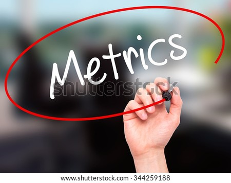 Man Hand writing  Metrics  with black marker on visual screen. Isolated on background. Business, technology, internet concept. Stock Photo - stock photo