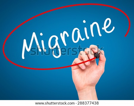 Man Hand writing Migraine with black marker on visual screen. Isolated on blue. Business, technology, internet concept. Stock Image - stock photo