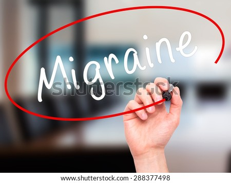 Man Hand writing Migraine with black marker on visual screen. Isolated on office. Business, technology, internet concept. Stock Image - stock photo